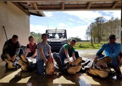 five men sitting on top of alligators