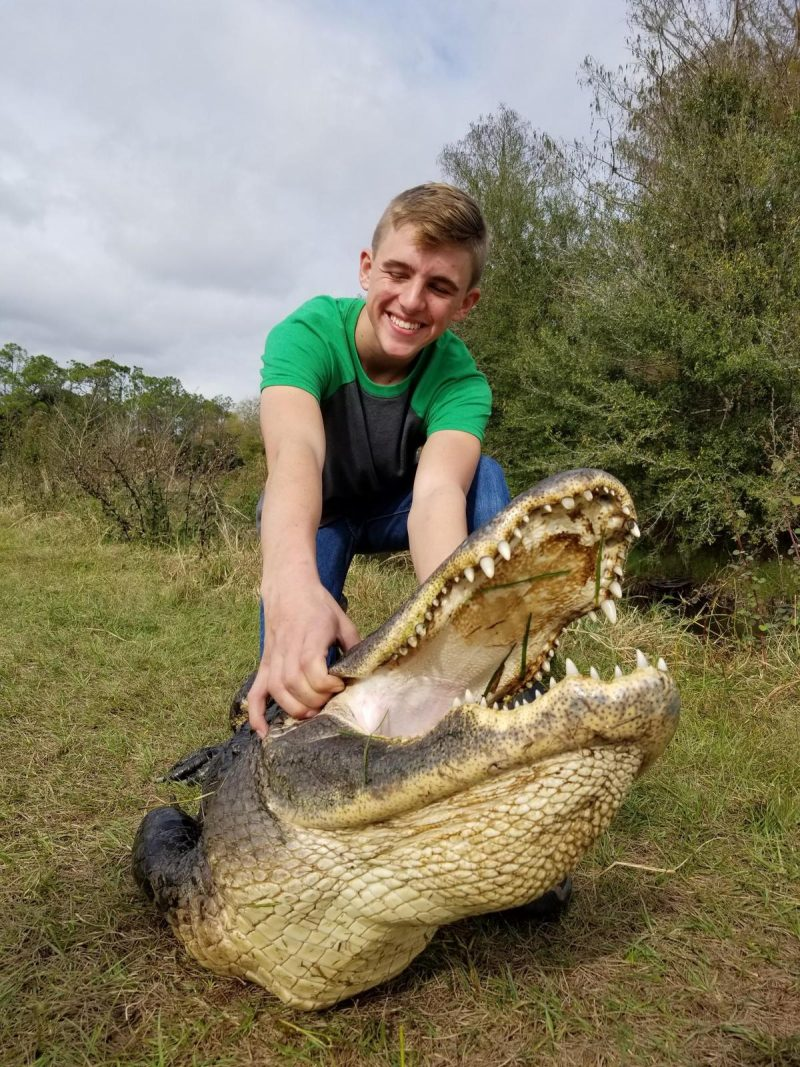 young man standing over alligator holding mouth open
