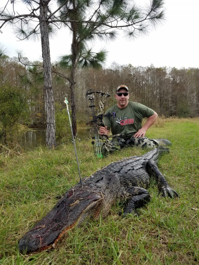 Man with bow sitting behind alligator