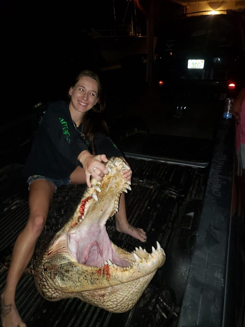 Girl sitting on top of an alligator