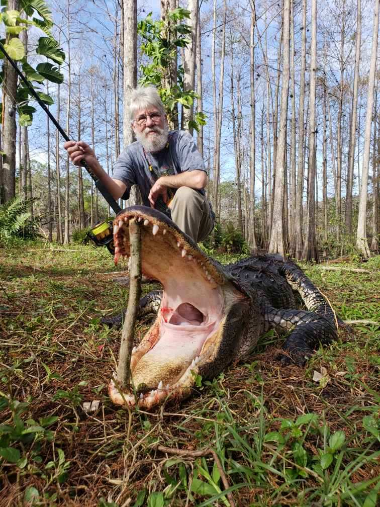 man kneeling behind alligator with its mouth open