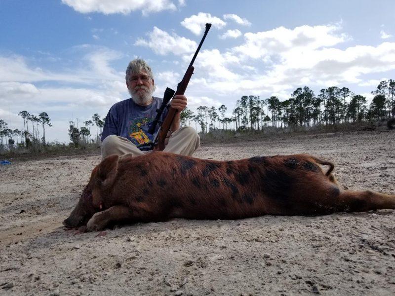 man sitting behind hog hunted in florida