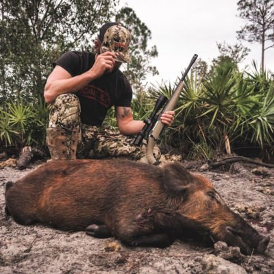 man with hog after hog hunting in florida