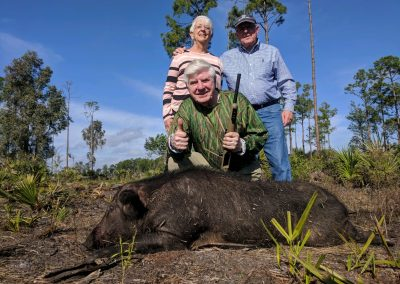 two men and a woman behind a hog they hunted in florida