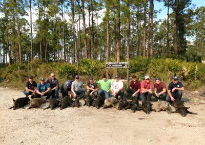 group of people kneeling behind hogs hunted in florida