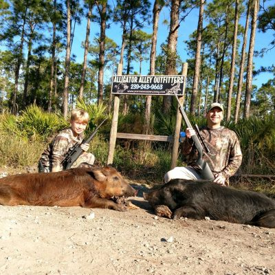 man and boy kneeling behind hogs during hunt special in florida