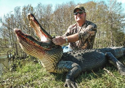 man holding gator by the mouth that he hunted in florida