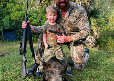 man and boy standing with hog hunted in florida
