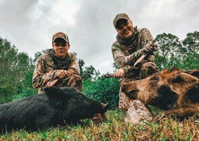 two men kneeling behind hogs hunted in florida