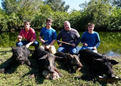 group of people kneeling behind hogs hunted in florida with knives