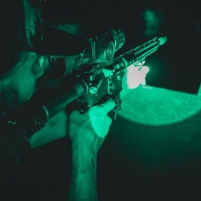 man holding riffle night vision hunt