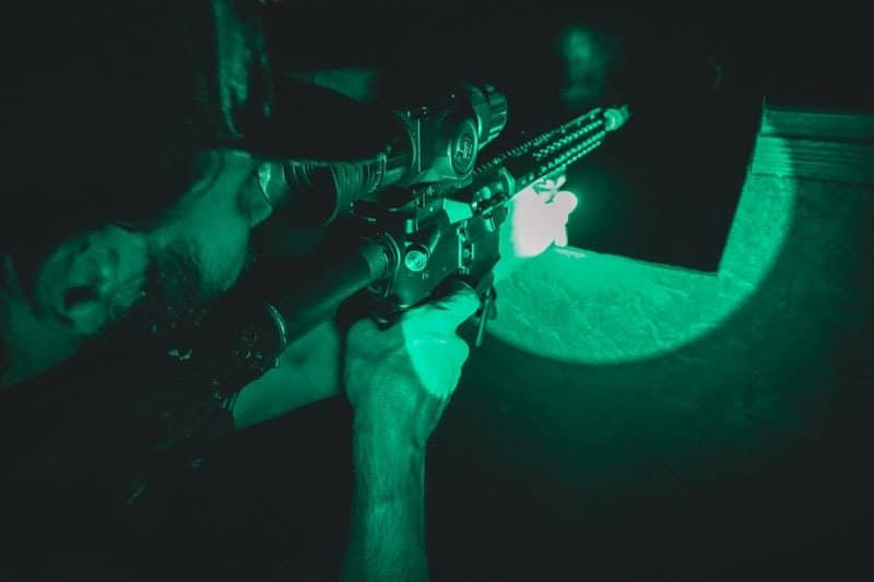 man holding riffle night vision hunt