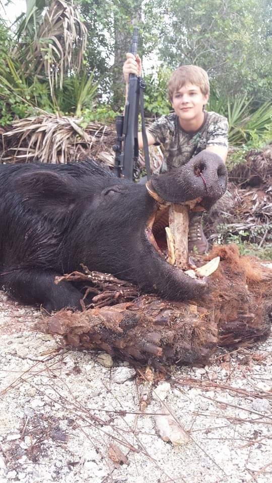 boy kneeling beside hog after hunting in south florida