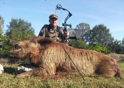 man with bow kneeling behind large hog after hunting in south florida