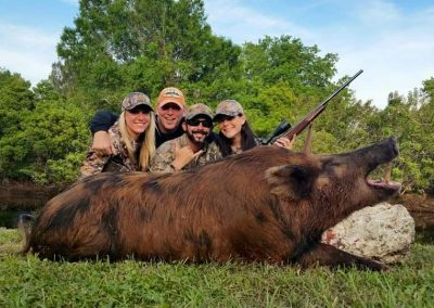 group of people kneeling behind large hog after hunting in South Florida